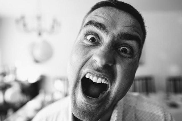 czarno białe zdjęcie krzyczącego mężczyzny który robi sobie selfie
