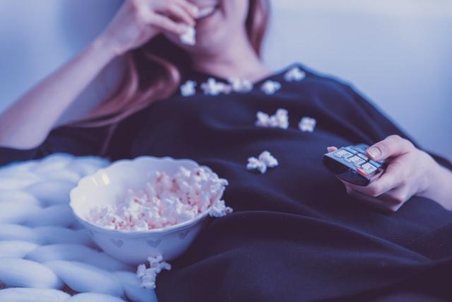 blondynka w czarnej bluzce leży na łóżku i objada się popcornem
