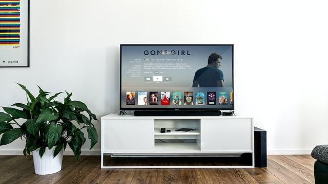 telewizor na białej szafce na tle białej ściany