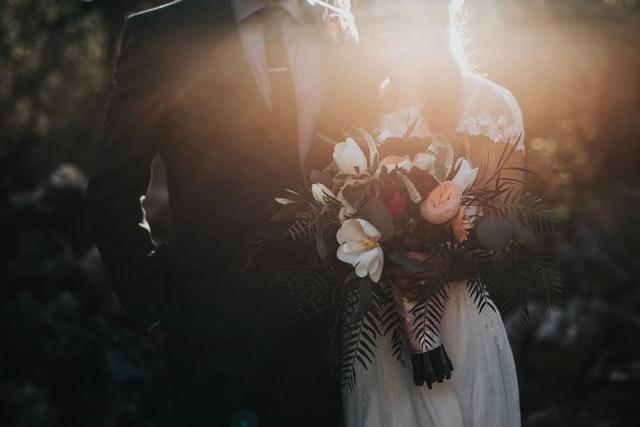 para młoda stojąca przodem w promieniach słońca i trzymająca przed sobą bukiet kwiatów