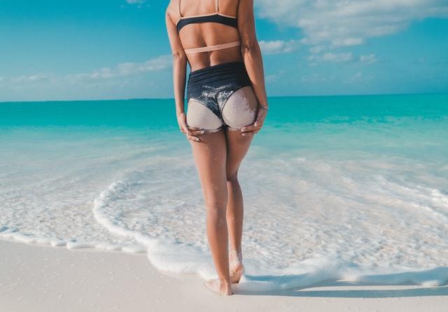 kobieta stojąca tyłem w czarnym bikini mająca pupę w piasku