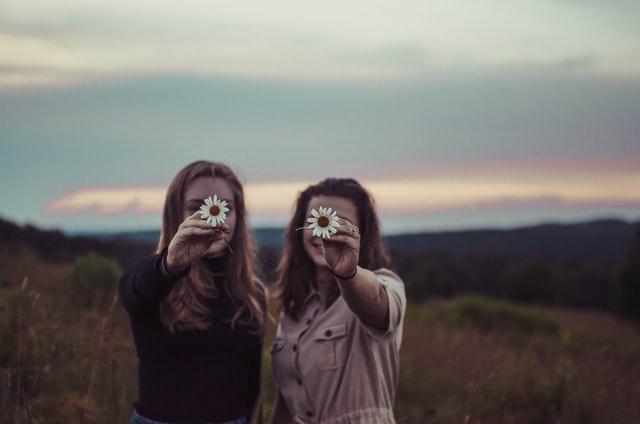 dwie dziewczyny zasłaniające sobie kwiatkami twarz
