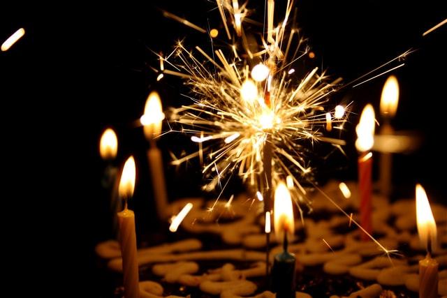 zimne ognie i świeczki wbite w tort przy zgaszonym świetle w pomieszczeniu