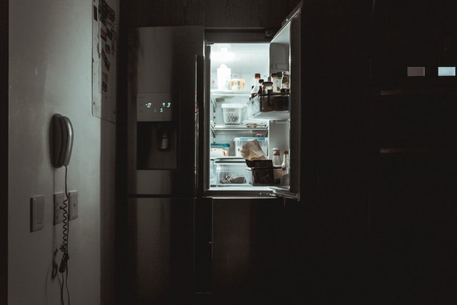wyłączone światło w kuchni i otwarta szeroko lodówka