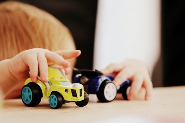 zbliżenie na dłonie małego dziecka, które bawią się autkami