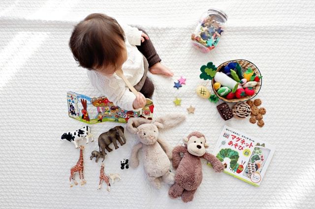 małe dziecko siedzi na białej podłodze i bawi się kolorowymi zabawkami