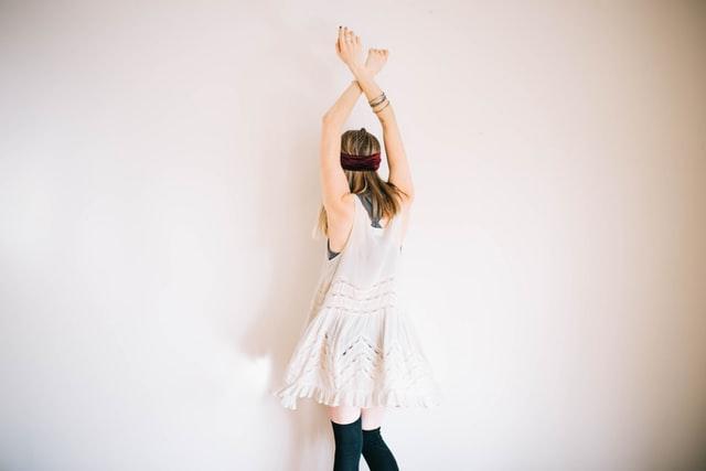 kobieta z wyciągniętymi rękoma ku górze stojąca na tle białej ściany