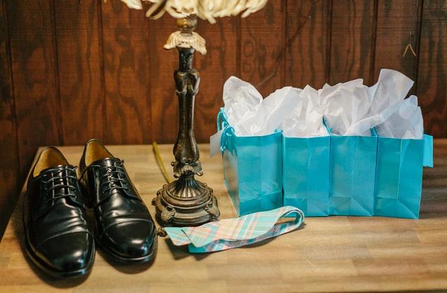 czarne eleganckie buty obok krawata i niebieskich ozdobnych torebek