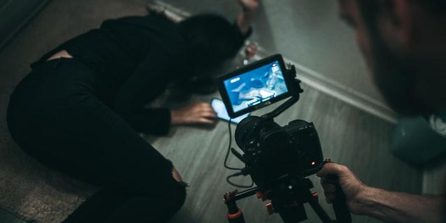 zbliżenie na kamerę kręcącą leżącą na ziemi kobietę