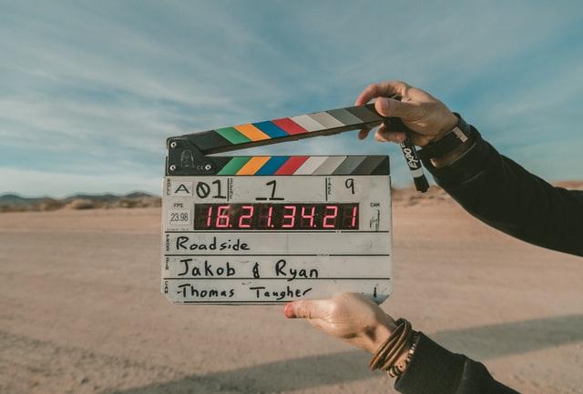 klaps filmowy w męskich dłoniach na tle pustyni