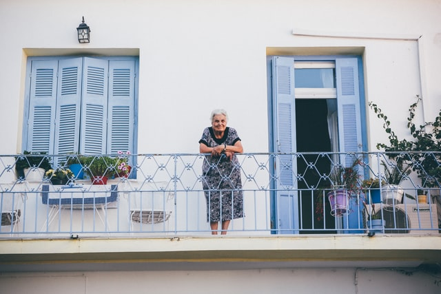 starsza kobieta stoi na balkonie i opiera się o balustradę