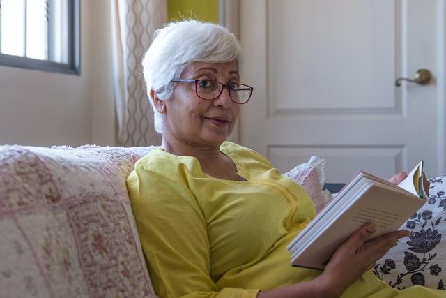 starsza kobieta ubrana na żółto siedzi na kanapie i czyta książkę