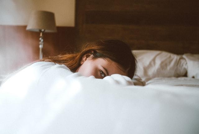 dziewczyna leżąca głową na łóżku na białej pościeli