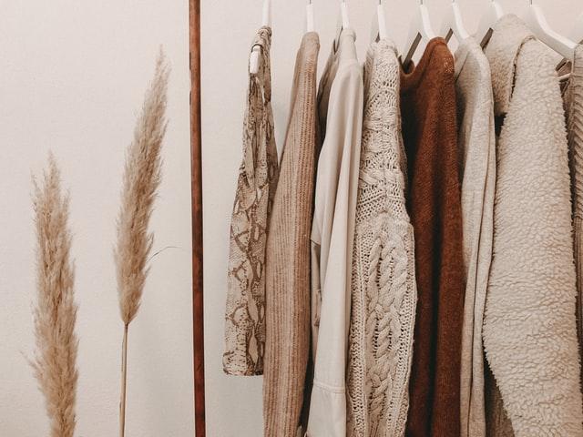 ubrania w beżowych i brązowych odcieniach wiszące na wieszaku stojącym na tle białej ściany