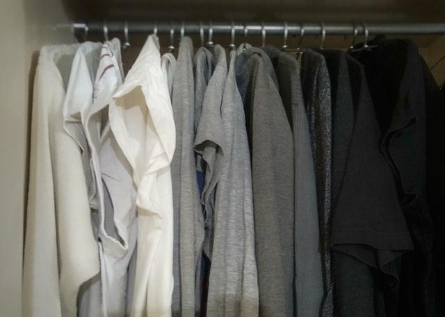 białe, szare i czarne ubrania powieszone na wieszakach w szafie