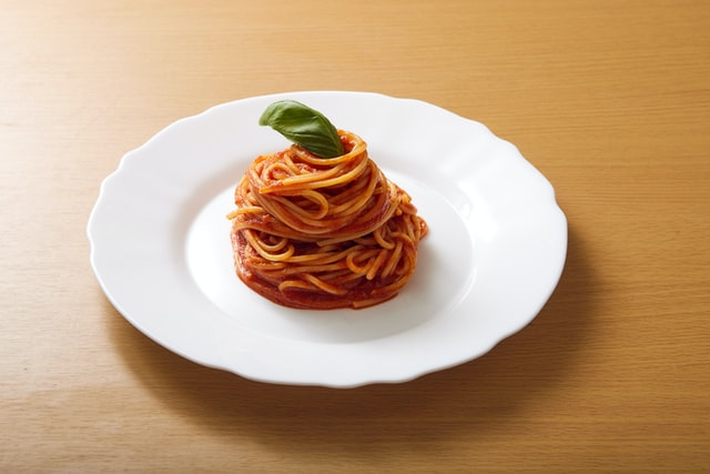 spaghetti na białym talerzu ozdobione liściem bazylii