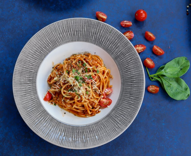 spaghetti na białym talerzu, które leży na niebieskim stole