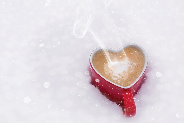 kubek w kształcie serca z gorącą kawą włożony do śniegu