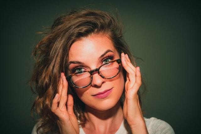 kobieta z zielonymi oczami z okularami na nosie, za które się trzyma