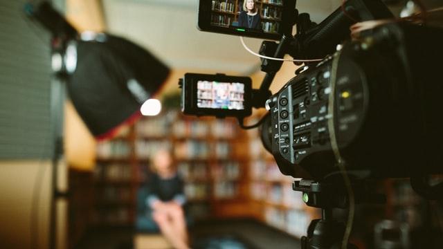 ekran kamery skierowany na kobietę siedzącą na tle biblioteczki