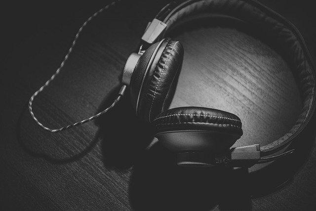 czarne słuchawki leżące na ciemnym blacie