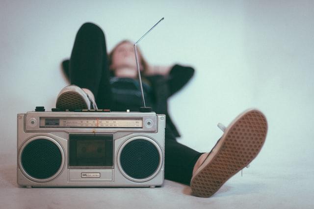 dziewczyna leżąca na plecach na podłodze trzymając nogę na radio