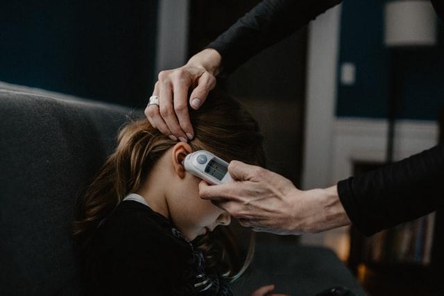 ktoś wkłada termometr do ucha małej dziewczynki ze spiętymi włosami