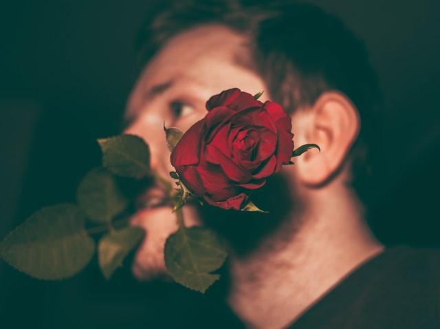 mężczyzna trzyma różę w zębach