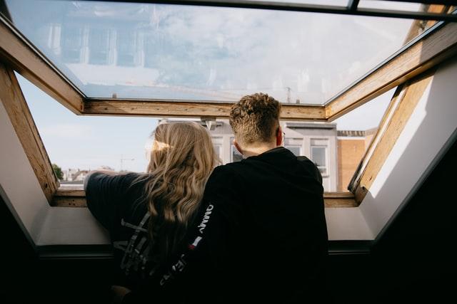 blondynka u boku mężczyzny patrzy przez okno
