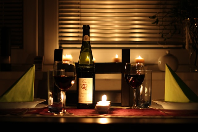 butelka wina i lampki na stole obok świeczki na tle okna