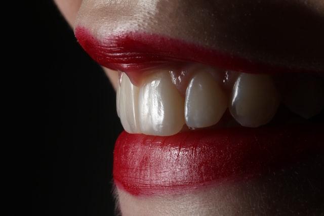 zbliżenie na białe zęby i czerwone usta