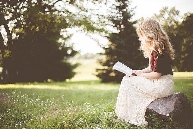 blondynka siedząca bokiem na ławce z książką na polanie a w tle choinki