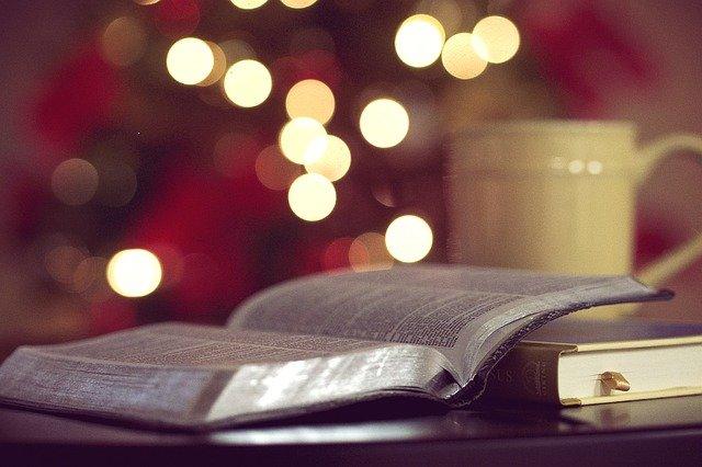 biblia otwarta na stole w tle świecące światełka