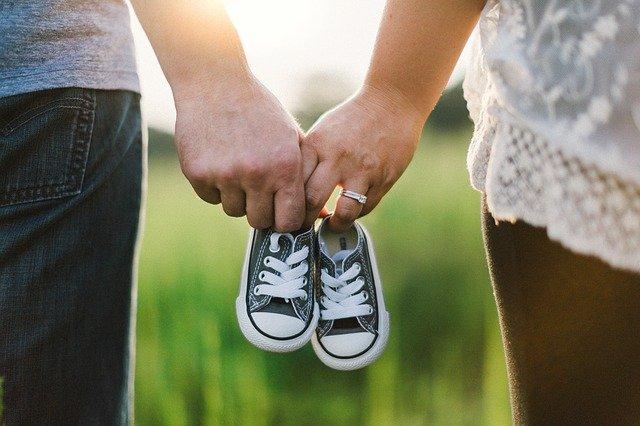 męska dłoń trzyma razem z damską dłonią malutkiego bucika dziecięcego na tle łąki
