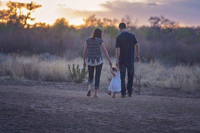 kobieta i mężczyzna trzymają za ręce małą dziewczynkę i idą po polanie tyłem