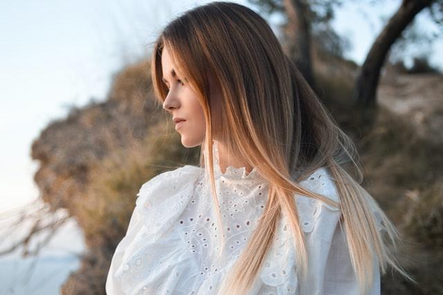 blondynka w rozpuszczonych włosach w białej bluzce spogląda w bok