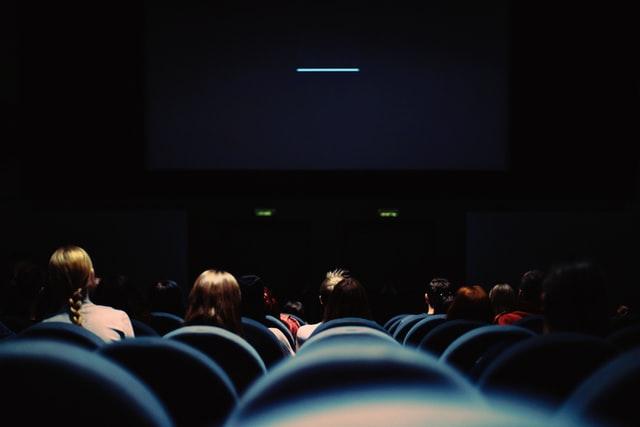 niebieskie siedzenia w kinie i ekran kinowy