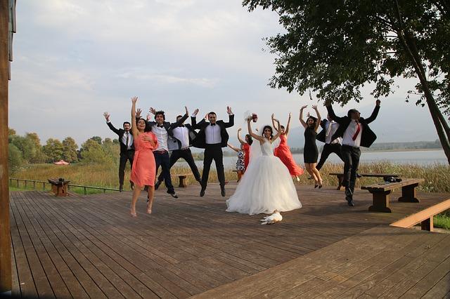 goście weselni i para młoda podskakują do góry