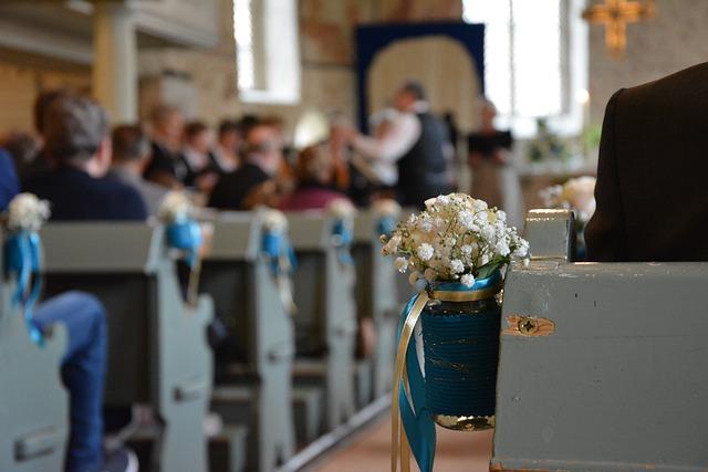 ławki w kościele ozdobione niebieską wstążką