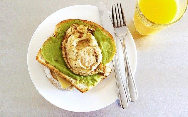 pasta jajeczna z dodatkiem awokado na grzance i na białym talerzu a obok sztućce