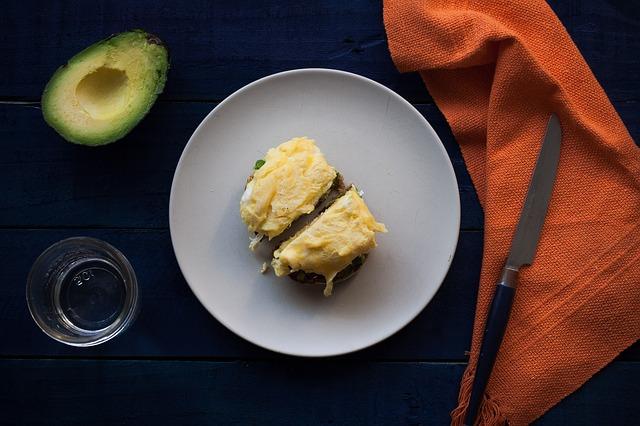 grzanka z jajkiem i awokado na białym talerzu, który leży na czarnym stole