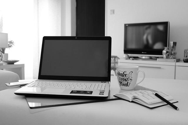 laptop leżący na stole a w tle na ścianie wisi telewizor