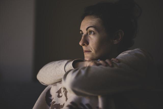smutna kobieta siedzi w ciemnym pomieszczeniu z założonymi rękoma na kolanach