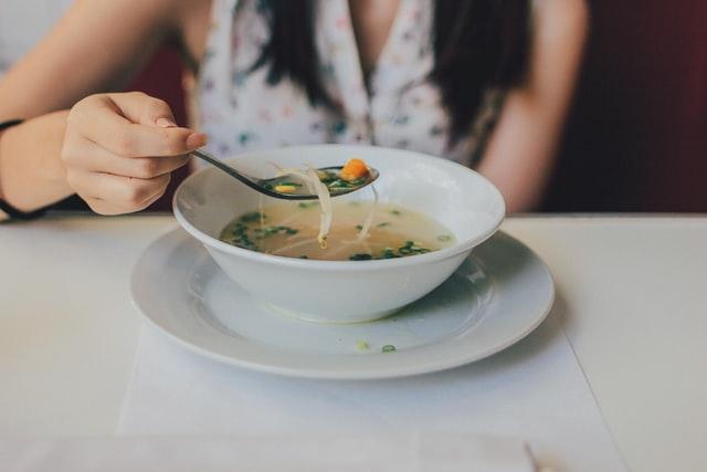 dziewczyna je zupę z białej zastawy stojącej na białym stole