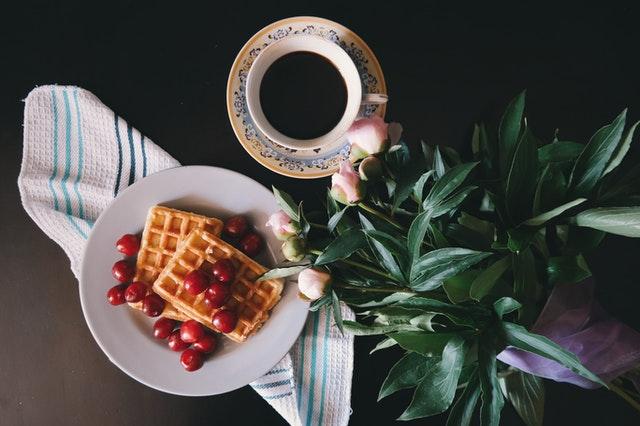 gofry położone na białym talerzyku na ciemnym blacie a obok nich kwiat doniczkowy i kawa