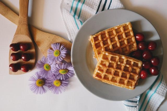 gofry położone na białym talerzyku a tuż obok fioletowe kwiaty