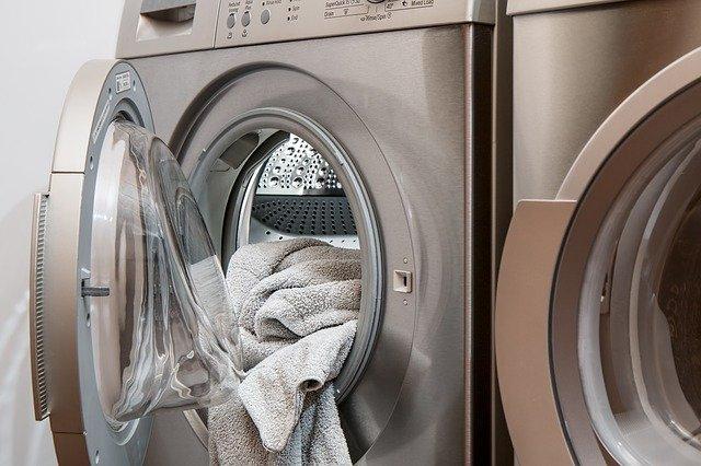 ręczniki włożone do otwartej pralki w kolorze srebrnym