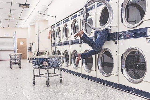nogi kobiety w dżinsach wystają z ogromnej pralki w pralni