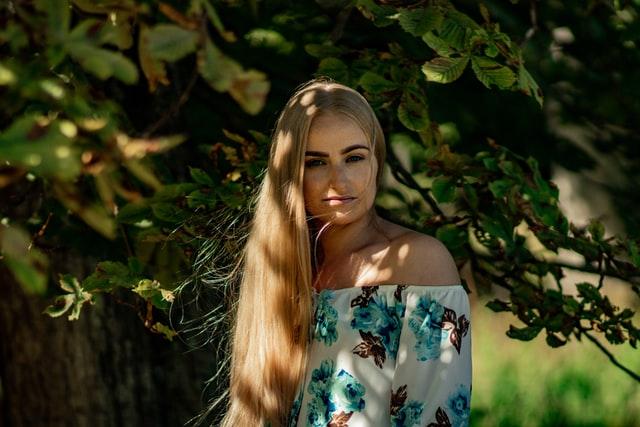 blondynka na tle drzew w kwiecistej bluzce opuszczonej na ramionach