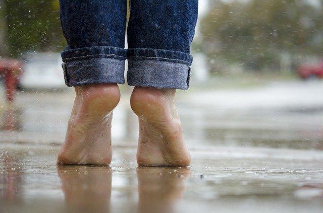 gołe stopy stojące na palcach na chodniku w czasie deszczu